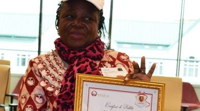 Annie Boma Kamuanya displays her FINCA Certificate of Loyalty in a picture frame.